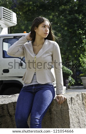 A teenage girl is sitting by a street./Take a break