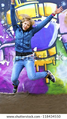 A teenage girl jumps in the trendy urban clothes fun on background of the wall with the image.