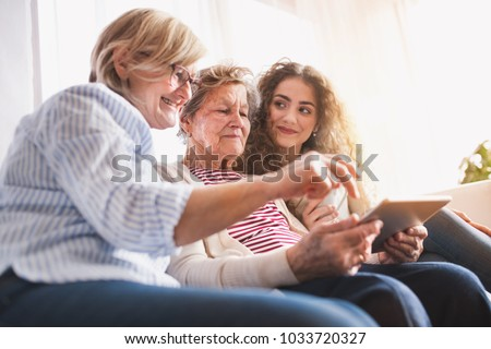 A teenage girl, mother and grandmother with tablet at home. #1033720327