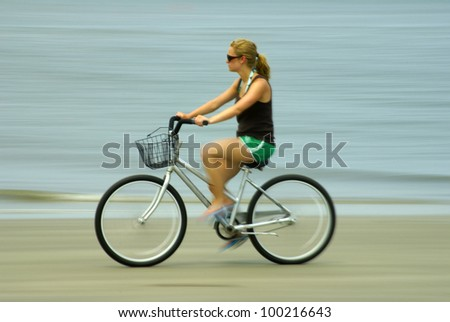 A teenage girl on a beach riding a bike. Panned to show motion.