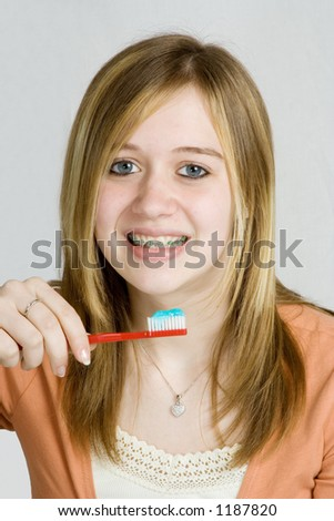 A teenage girl prepares to brush her teeth with braces.