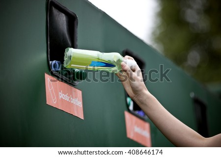 A teenage girl recycling a plastic bottle