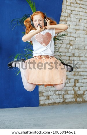 A teenage girl sings, dances and jumps. The concept is childhood, lifestyle, music, singing, listening, hobbies. #1085914661
