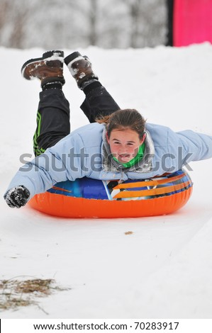 A teenage girl sleds down a snow covered hill