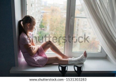 A teenage girl with a broken leg in a cast is sitting on a windowsill with crutches.