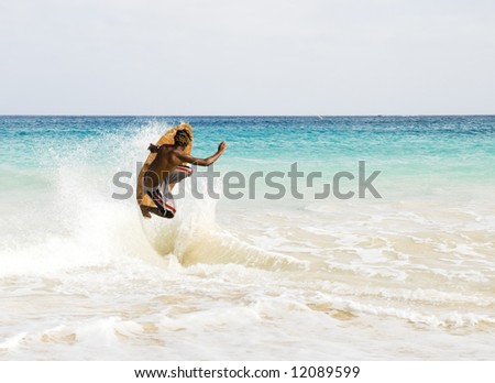 A teenage skimboarder jumping a wave.