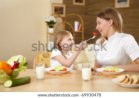 a teenaged daughter with her mother in th ekitchen at home having meal together