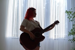 A teenager girl silhouetted against the background of the window plays the guitar