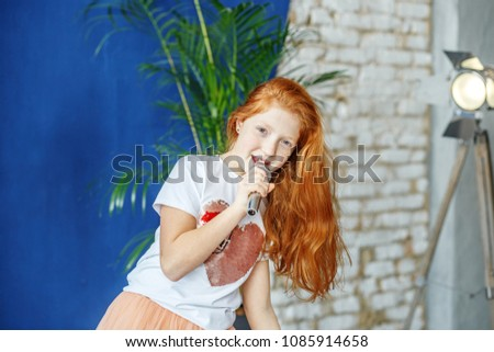 A teenager girl sings a song into a microphone. The concept is childhood, lifestyle, music, singing, listening, hobbies. #1085914658