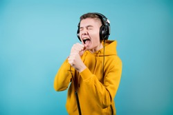 a teenager in a yellow sweatshirt on a blue background sings or screams into the plug from the large headphones that are worn on it