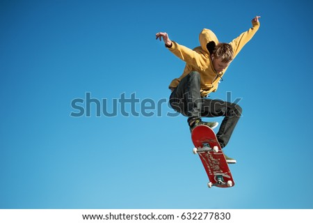 Photo of  A teenager skateboarder does an ollie trick on background of blue sky gradient