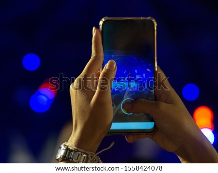 A teenager using a mobile phone. Take a free concert atmosphere #1558424078