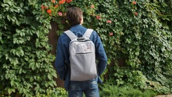 A teenager, wearing a denim jacket and a rucksack with communist pins among the vine in summer.
