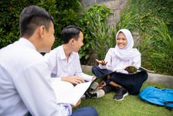 a teenager wearing a headscarf in school uniform gave an explanation by holding a book while studying with his male friends while sitting on the grass in the park