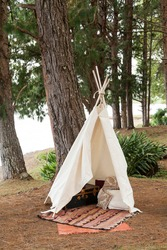 A teepee tent made of raw cloth in the middle of the forest.