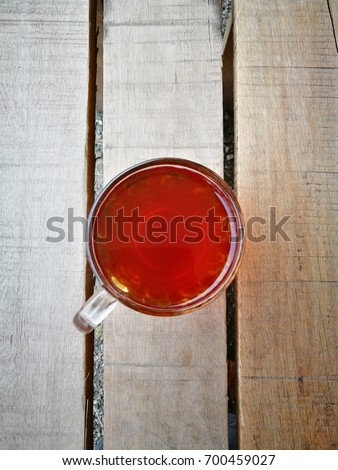 """A """" TEH O """" or in English, plain tea served in a glass. Served on wooden table. Famous drink in Malaysia. #700459027"""