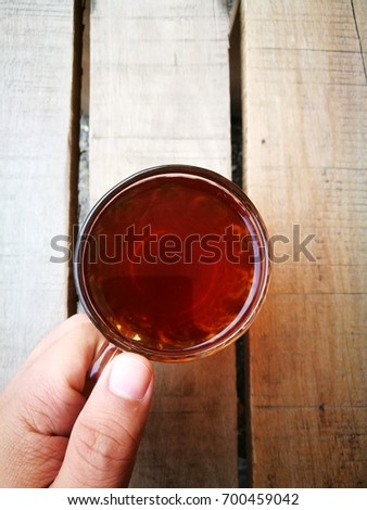 """A """" TEH O """" or in English, plain tea served in a glass. Served on wooden table. Famous drink in Malaysia. #700459042"""