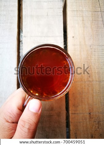 """A """" TEH O """" or in English, plain tea served in a glass. Served on wooden table. Famous drink in Malaysia. #700459051"""
