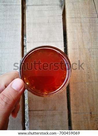 """A """" TEH O """" or in English, plain tea served in a glass. Served on wooden table. Famous drink in Malaysia. #700459069"""