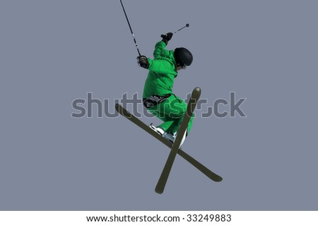 a Tele-hele. A skier executes a perfect crossed skis tele-heli during a high jump isolated on gray background