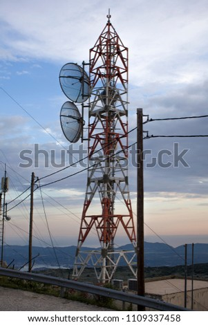 A telecom tower with two parabolic antennas with pylon carrying cables. It uses a parabolic reflector, a curved surface with the cross-sectional shape of a parabola, to direct the radio waves. #1109337458