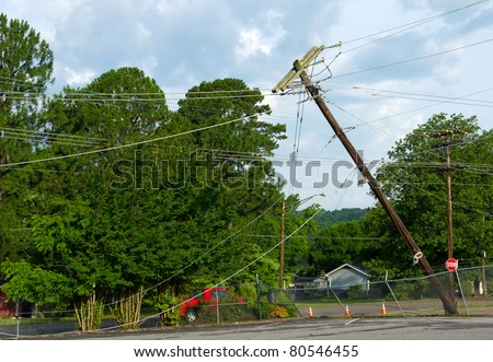 A telephone pole leans after damage from a storm.