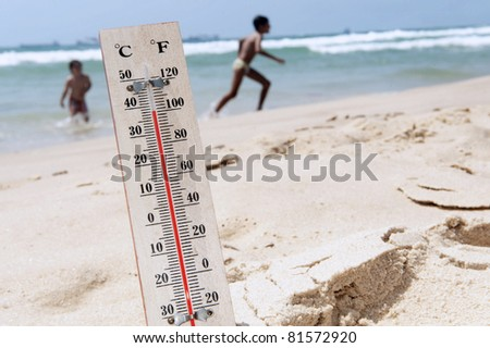 A temperature scale on a beach with people in the background shows high temperature during a heat wave. Concept photo of heat wave , warm weather, global warming, high temperatures, climate change.