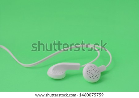 A template for music listening fans. White earphones on green