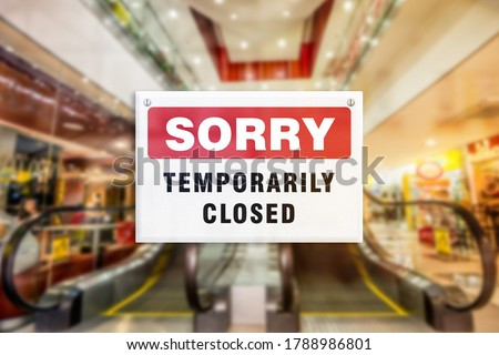A temporary closure sign of a shopping mall. Concept of Closure, suspension, or bankruptcy of shopping center. Blurred escalator. ストックフォト ©