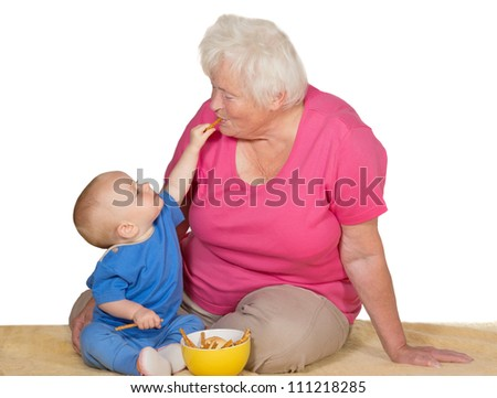 A tender moment as an adorable small baby reaches up with a biscuit to place it in the grandmothers mouth as the two sit on a carpet on the floor