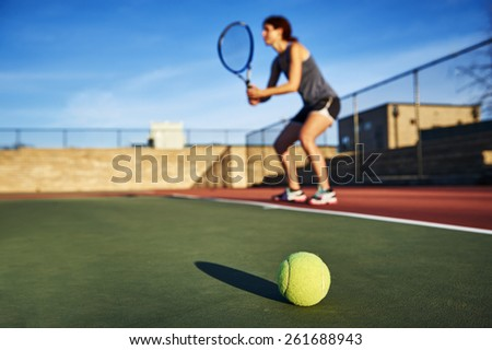 a tennis ball and young woman holding a tennis racquet in background.  focus on tennis ball.