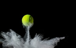 A tennis ball bouncing in chalk dust with black background. Conceptual, signifying ball hitting the line