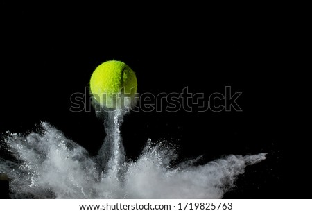 A tennis ball bouncing in chalk dust with black background. Conceptual, signifying ball hitting the line Stockfoto ©