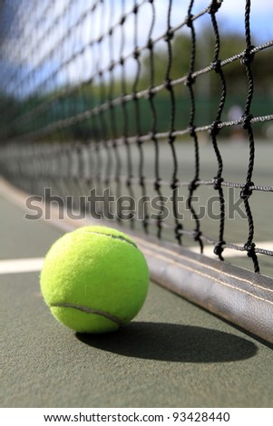 A tennis ball lies on the court next to the net