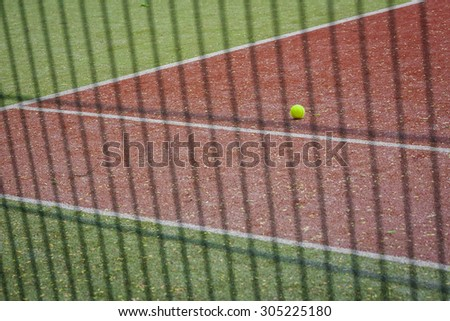 A tennis ball on the tennis court, the view through the fence.