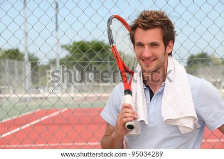 A tennis player posing in front of a tennis court with his racket.