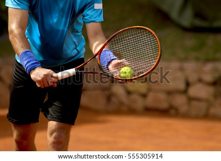 A tennis player prepares to serve a tennis ball during a match