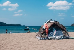 A tent pitched at a public beach, in the middle of the scorching day. Clothes and towels are on top outside to dry. Camping in Nasugbu, Batangas, Philippines.