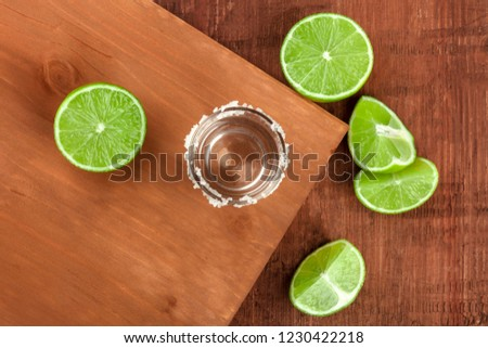A tequila shot with limes, shot from above on dark rustic textures with a place for text #1230422218