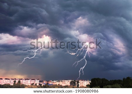 A terrible dangerous storm with a strong wind swirls thunderclouds in the mountains with fabulous twists, from which rain and hail or a thunderstorm with lightning flies.