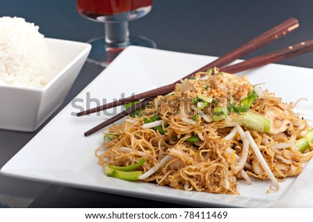 A Thai dish of chicken and noodles stir fry presented on a square white plate with wooden chopsticks.