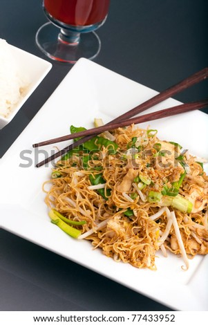 A Thai dish of stir fried chicken vegetables noodles jasmine rice and bean sprouts on a large white plate with chop sticks.