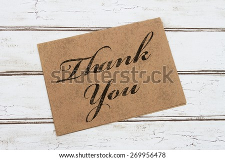 A thank you card, A brown card with words Thank You over a distressed wood background