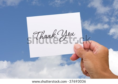 A thank you card sitting in hands on a sky background, blank card - stock photo