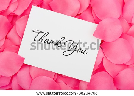 A thank you card sitting on a pink flower petal background, thank you with love