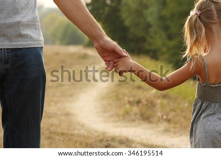 a the parent holds the hand of a small child #346195514