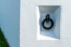 A thick black cast iron or wrought iron ring anchored in a wide white concrete wall at a marina for securing boats. The black round forged bolted rigging chains boats or winch items at a dock.