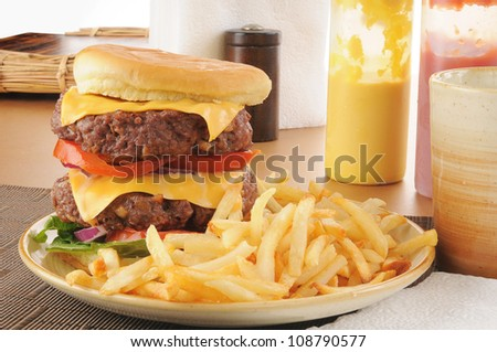 A thick double decker hamburger with fries