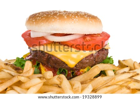 A thick, fresh, juicy hamburger with all the trimmings rests next to a pile of salty French fries.  Image isolated on white for use in any promotional inferences.