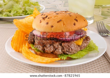 A thick grilled cheeseburger on an onion bun